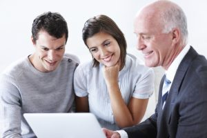 Attractive young couple with their financial advisor showing them their options on his laptop